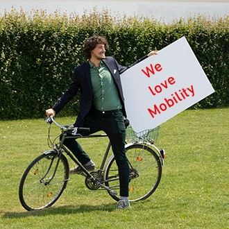 """Mitarbeiter hält Schild mit """"We love Mobility"""" darauf"""